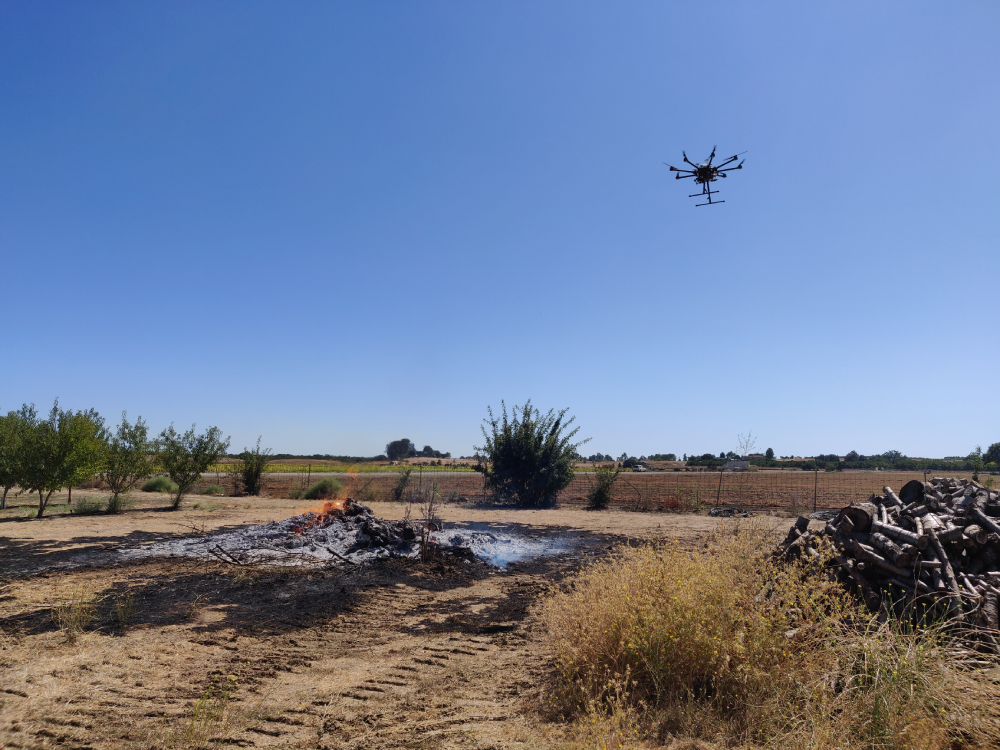 A drone flies near a controlled burn to conduct tests. Mechanical and aerospace engineers at UC Davis think drones are perfect for monitoing the chemical composition and propagation of wildfire smoke. (Zhaodan Kong/UC Davis)